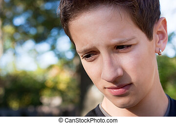 Unsure Boy - Young teen looking uncertain against an outdoor...
