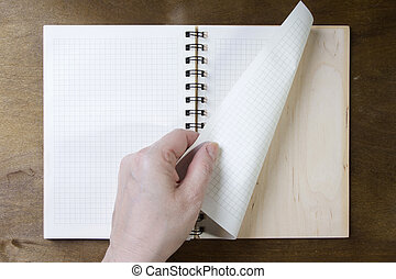 Hands turn pages of the notebook