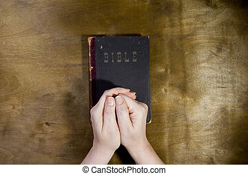 Woman with Bible - Hands of an unrecognizable woman with...