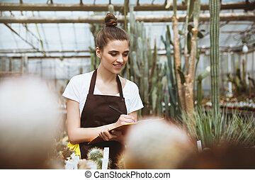 Happy young lady standing in greenhouse holding clipboard -...