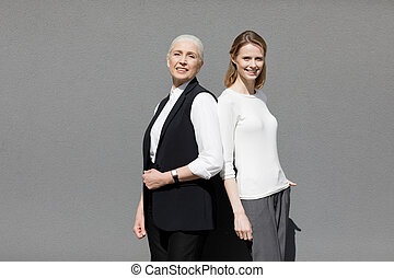 Two beautiful smiling women standing back ro back isolated...