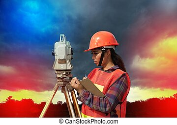 Surveyor or Engineer making measure by Theodolite with partner on a field.