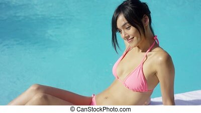 Exotic brunette wearing pink bikini sun bathes while leaning...