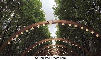Wooden arch with lanterns - In city park passage under...