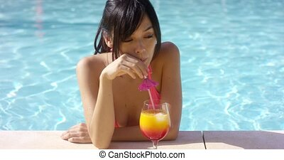 Pretty young woman sipping a tropical cocktail as she cools...