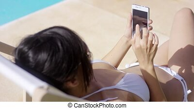 Young woman browsing on a mobile in the summer sun as she...