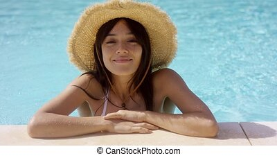 Woman in straw hat and swim suit stands in pool with elbows...