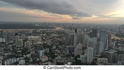 Modern city during beautiful cloudy sunset - Aerial drone...