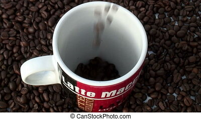 Coffee beans are tumbling in a cup