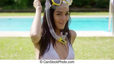 Blissful young woman in snorkel and goggles standing in her...