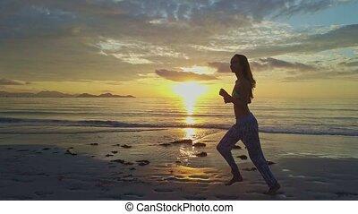 Girl Silhouette Runs along Beach against Rising Sun Path -...