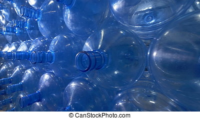 A stack of empty 5 gallon bottles. - Many 5 gallon plastic...