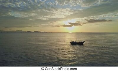 Single Boat Sails in Ocean against Sun Path at Dawn - small...