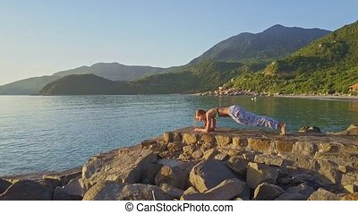 Flycam View Girl Does Yoga against Hilly Landscape on Coast...