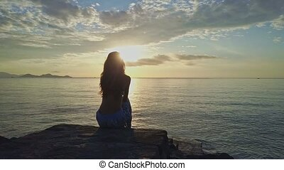 Girl Silhouette Sits on Beach Rock Watches Bright Sunrise -...