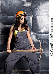 Beautiful sexy worker with a pickaxe. Seductive and...