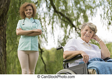 Nurse and senior woman on a wheelchair in garden - Smiling...