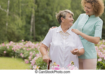 Nurse and elderly woman with a cane in a garden