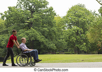 Man pushing disabled person on wheelchair