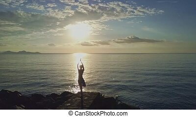 Drone Moves to Girl Doing Yoga against Sunrise Boundless Sea