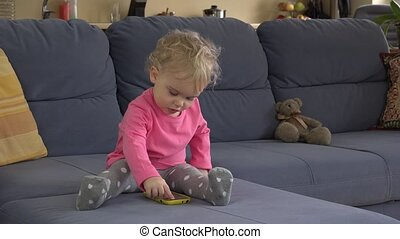 baby girl use modern smart mobile phone sit on sofa in room....