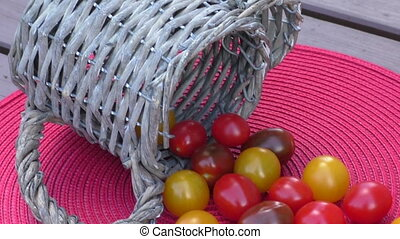 Various of colorful cherry tomatoes in a small basket on an red surface