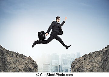 Risk concept - Side view of young businessman jumping over...
