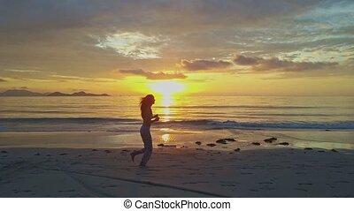 Girl Silhouette Jogs on Wet Beach against Rising Sun...