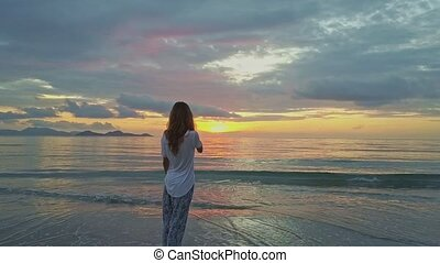 Flycam Shows Woman Making Video of Dawn above Ocean in...