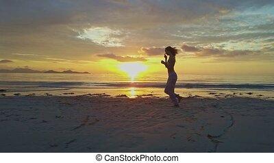Slim Girl Jogs Barefoot on Wet Beach against Ocean Sunrise -...