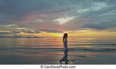 Woman in White Blouse Walks on Wet Sand Beach at Dawn in...
