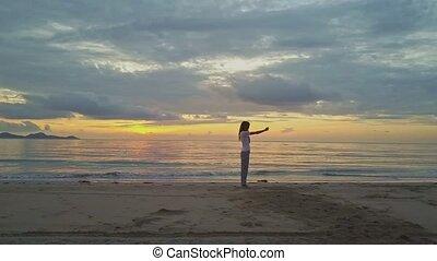 Girl Makes Selfie on Beach against Golden Sunrise above...