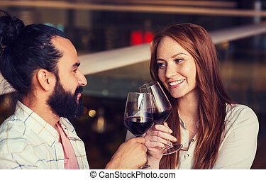 couple drinking red wine and clinking glasses