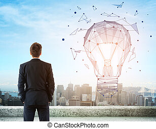 Man looking at lamp - Businessman on rooftop looking at...