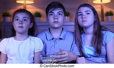 Children watching scary movie on TV - Group of children...
