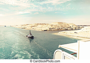 The Suez Canal - a ship convoy with a cruise ship passes...