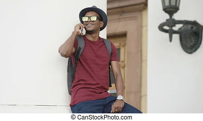 African american tourist man chatting with smartphone...