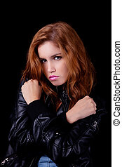 young and beautiful woman, with arm crossed in the form of an x, isolated on black background. Studio shot