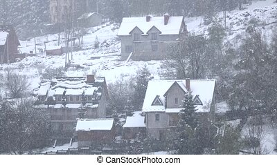 Snowfall calmly and quietly falls on village of wooded hill,...