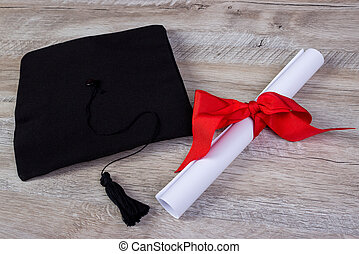 graduation cap, hat with degree paper on wood table...