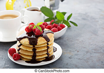 Stack of fluffy buttermilk pancakes with chocolate syrup and...