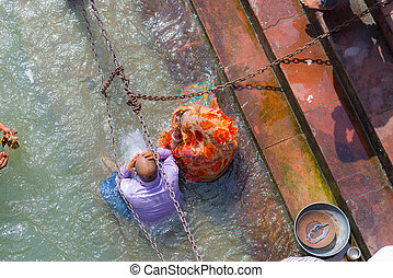 Haridwar, India - March 11, 2017: unidentified people bathing and taking ablutions in the Ganges River at the Holy ghats in Haridwar, India, sacred town for Hindu religion.