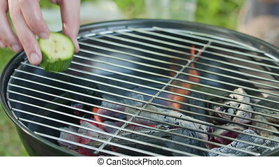 Barbecue Grill. Putting Marrows on Grate - Barbecue grill....