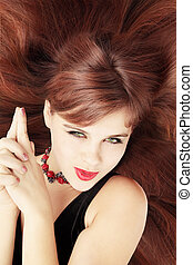 Red-haired coquette - Red-haired coquettish young woman lies...