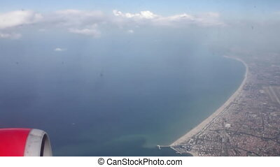 View through airplane window on sea and shore landscape and engine
