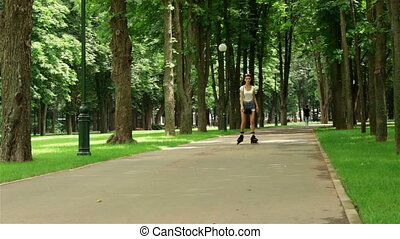skinny women in shorts is riding on rollers in a park -...