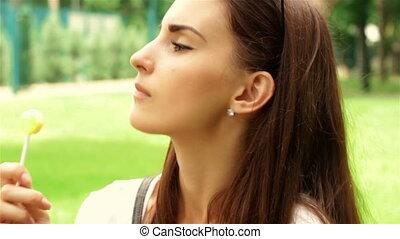 attractive young brunette sucks lollipop in Park