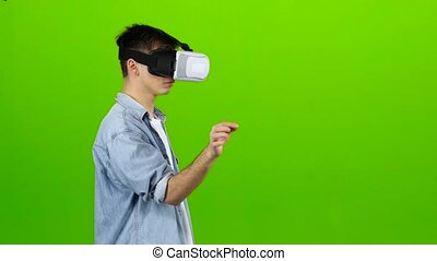 Man in virtual reality glasses is building graphics. Green...