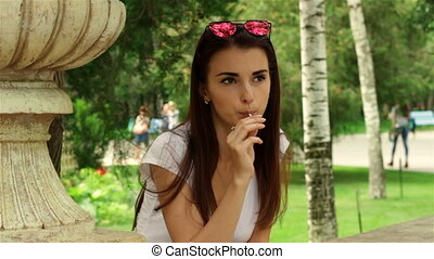fashionable girl with sunglasses looks to the side and licks a lollipop