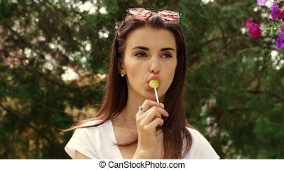 woman looks straight and sucks lollipop - a young woman...